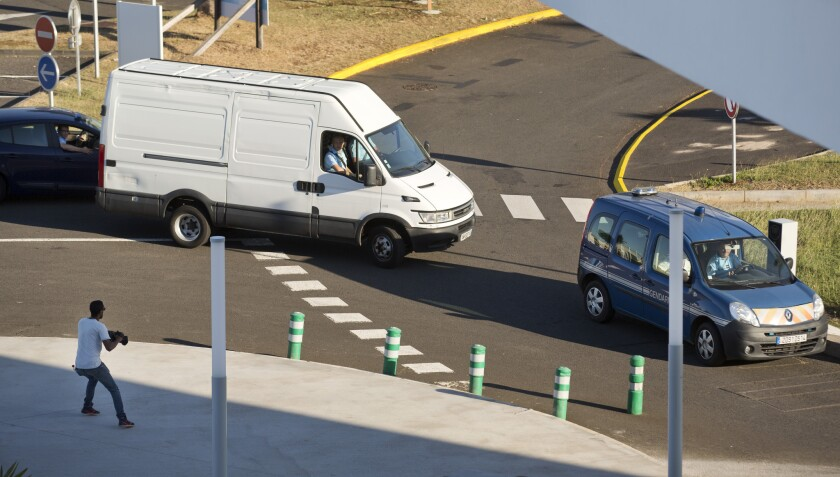 A white van carrying the airplane wing part that washed up on Reunion Island is escorted by the French gendarmerie to a cargo hangar at the island's Roland Garros Airport in Sainte-Marie on July 31.