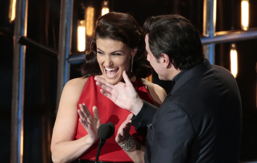 Idina Menzel and John Travolta in the midst of the chin-grabbing during Sunday's 87th Academy Awards at the Dolby Theatre.