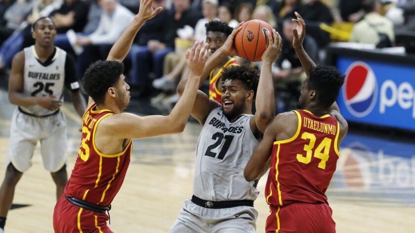 Colorado forward Evan Battey, center, is trapped with the ball by USC forwards Bennie Boatwright, left, and Victor Uyaelunmo in the second half.