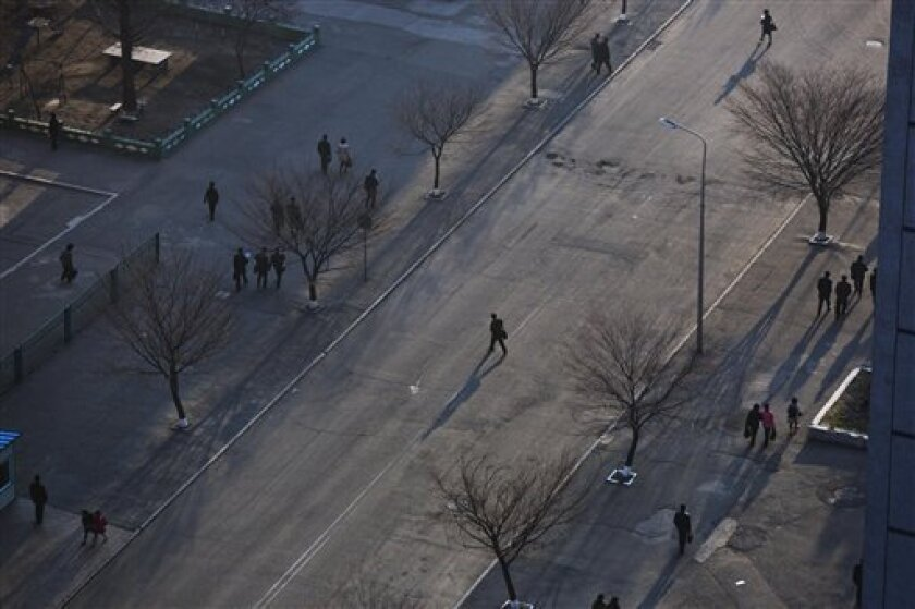 A North Korean commuter crosses a street in central Pyongyang on Wednesday, April 10, 2013. (AP Photo/David Guttenfelder)