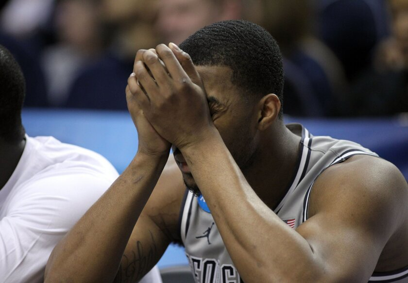 Georgetown forward Mikael Hopkins sits on the bench with head in hands during the final moments of an NCAA college basketball tournament round of 32 game against Utah in Portland, Ore., Saturday, March 21, 2015.  Utah beat Georgetown 75-64. (AP Photo/Craig Mitchelldyer)