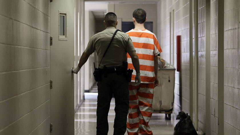 In this Feb. 21, 2013, file photo, an inmate at the Madera County Jail is taken to a housing unit at the facility in Madera, Calif.