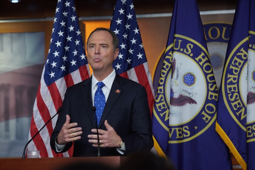 Adam Schiff speaks at a lectern in front of a row of flags.