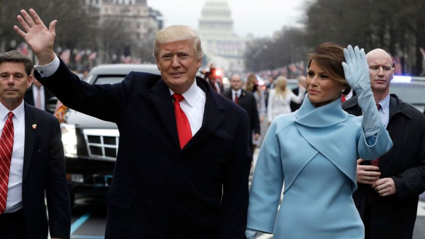President Donald Trump waves as he walks with first lady Melania Trump during the inauguration parad
