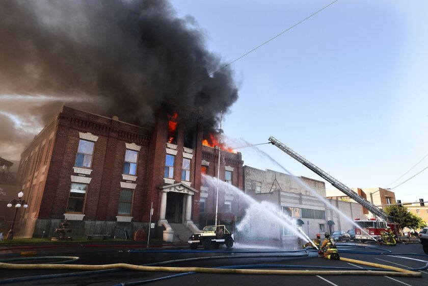 The old City Hall building burns as firefighters from all over Umatilla County battle the blaze in Pendleton, Ore., Tuesday, July 21, 2015. An explosion and fire destroyed part of the city's former government building. (E.J. Harris/East Oregonian via AP)