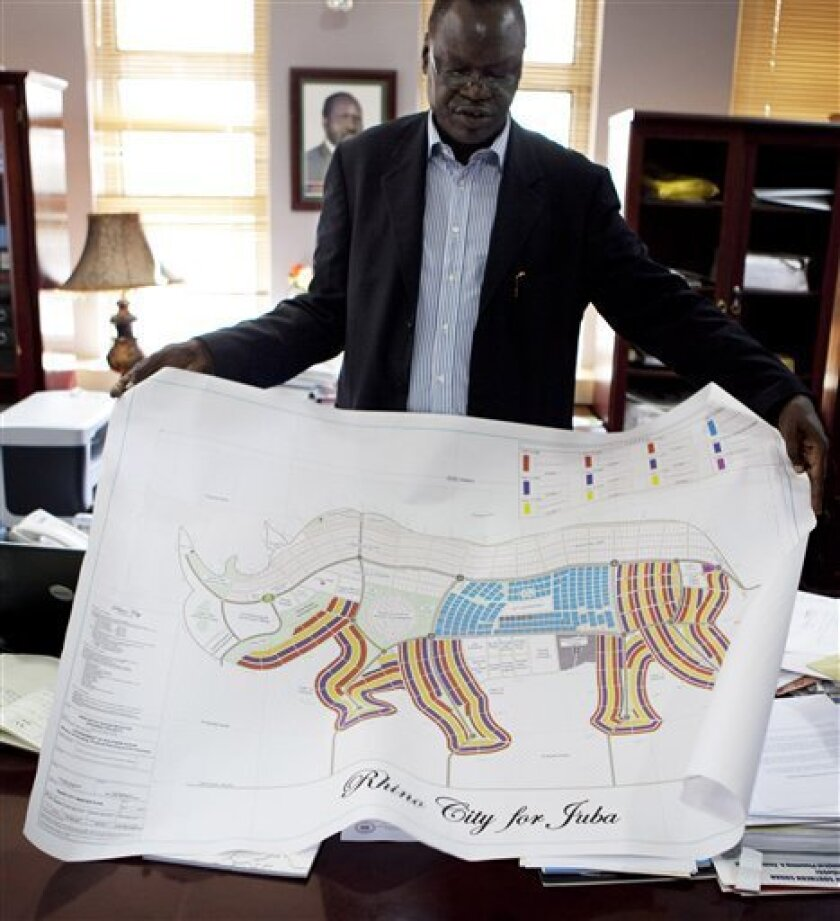 Dr. Daniel Wani, Undersecretary for the Ministry of Housing and Physical Planning in the Government of South Sudan, explains a map of Juba in the shape of an rhino, Wednesday, Aug 18, 2010, in Juba, Southern Sudan. A city shaped like a giraffe? A rhino-shaped town? Even one like a pineapple?Southern Sudan has unveiled ambitious plans to remake its capital cities in the shapes found on their state flags, and an official says the government is talking with investors to raise the $10 billion the fanciful communities would cost.(AP Photo/Pete Muller)