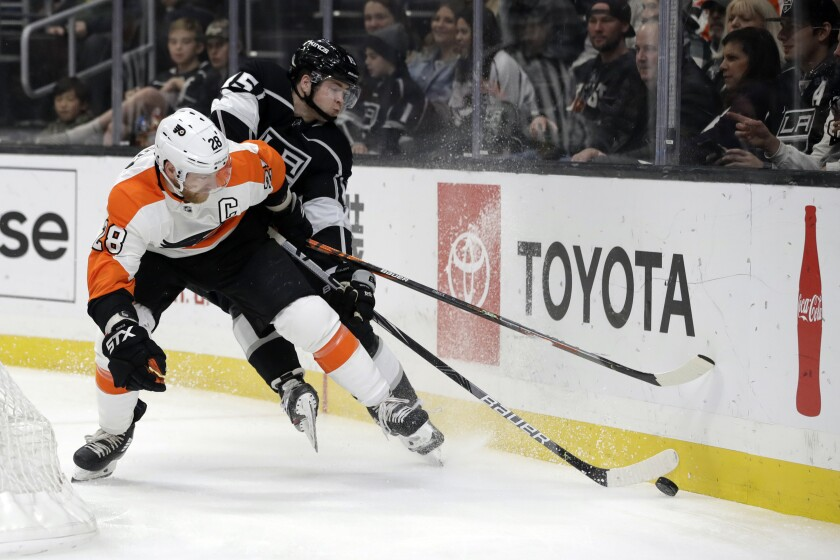 Flyers center Claude Giroux and Kings defenseman Ben Hutton battle along the boards behind the net during the first period of a game Dec. 31 at Staples Center.