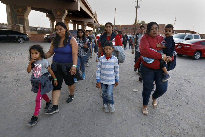 A group of men, women and children are led by U.S. border patrol agents and police to a holding area after they crossed into the U.S. to seek asylum. A new policy may strip unaccompanied minors of their protected status.