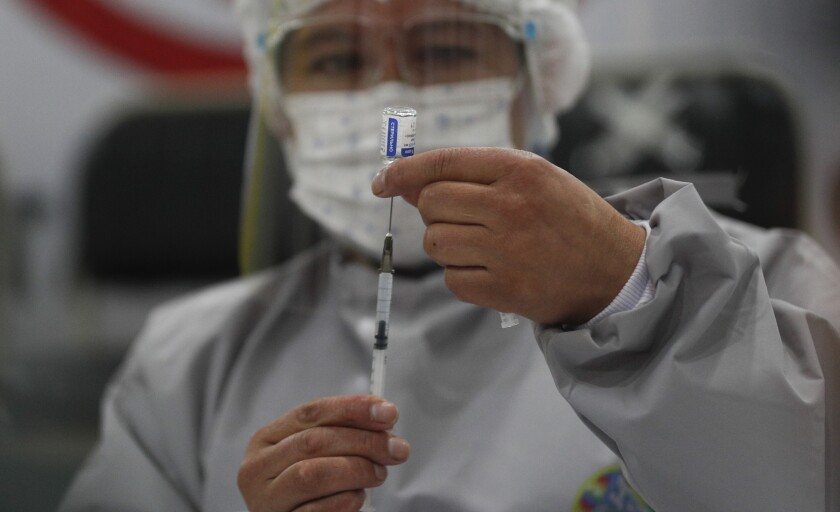 Healthcare worker preparing dose of Russia's COVID-19 vaccine