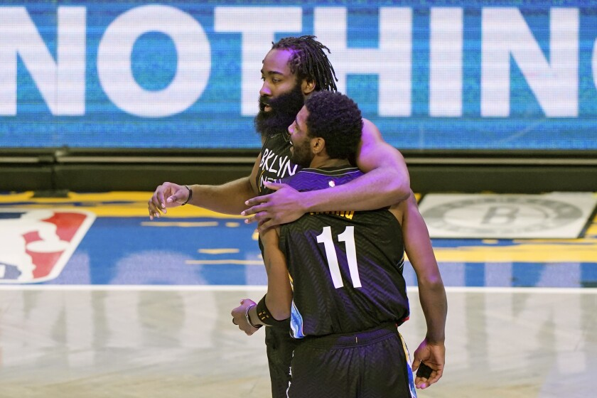 James Harden puts an arm around teammate Kyrie Irving.
