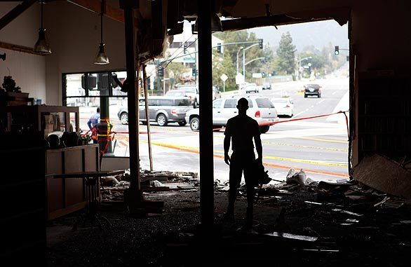 Workman Bill Andrew looks north out the front of the Flintridge Bookstore and Coffeehouse as vehicles descend Angeles Crest Highway toward La Cañada Flintridge's Foothill Boulevard. A big rig descending Angeles Crest barreled through the busy intersection on Wednesday, struck several vehicles and smashed into the bookstore/coffeehouse, killing two motorists and injuring 12 people, three of them critically.