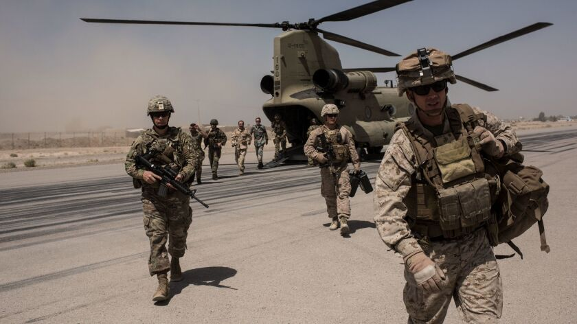 U.S. service members walk off a helicopterat Camp Bost in Helmand Province, Afghanistan.