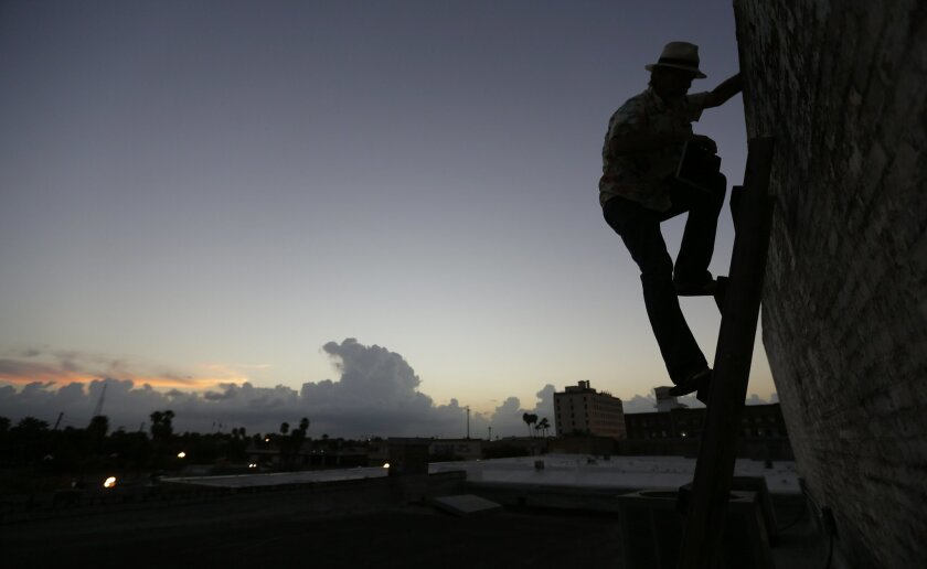 "CORRECTS NUMBER OF MILES FENCE RUNS IN TEXAS FROM 54 TO ABOUT 100 MILES - In this Sept. 16, 2015, photo, artist Mark Clark, who's studio is located near the border fence, climbs to his rooftop to watch for activity along the border, in Brownsvill, Texas. The staggered fence or ""wall,"" costing $6.5 million per mile, runs along about 100 miles of Texas' 1,254-mile border with Mexico. (AP Photo/Eric Gay)"