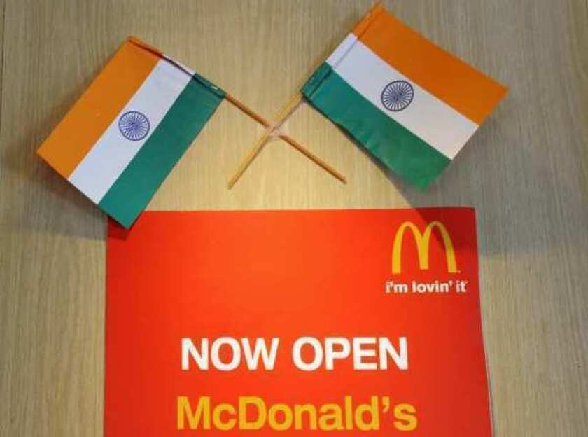 Two Indian flags adorn a sign at a local McDonalds chain restaurant in New Delhi. The fast food giant will open two vegetarian branches in the country.
