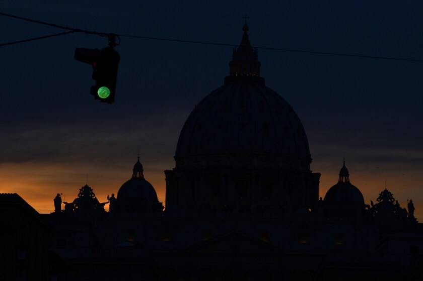 A green traffic light is shown next to the silhouette of St. Peter's basilica at night.