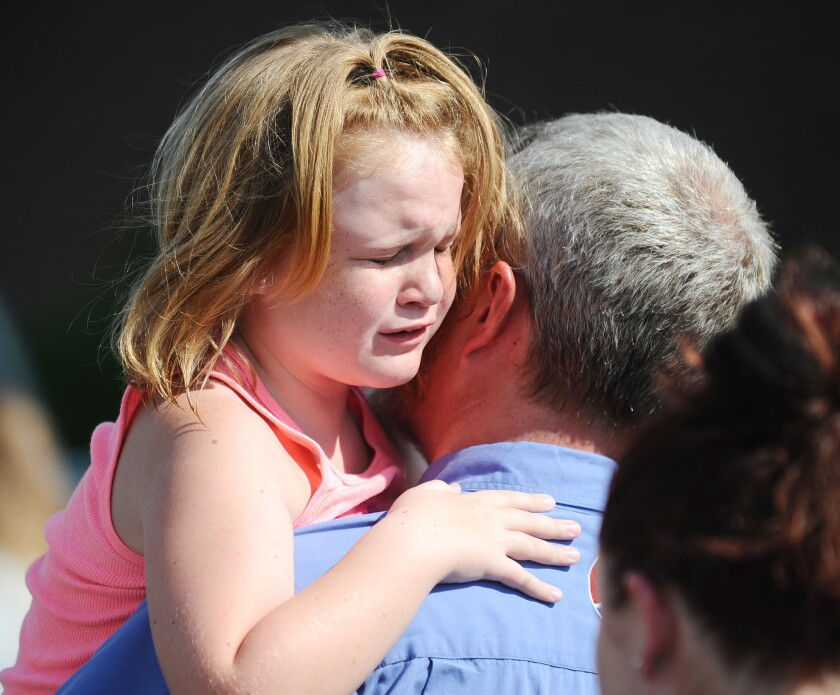 Lilly Chapman, 8, cries after being reunited with her father, John Chapman at Oakdale Baptist Church on Wednesday in Townville, S.C.