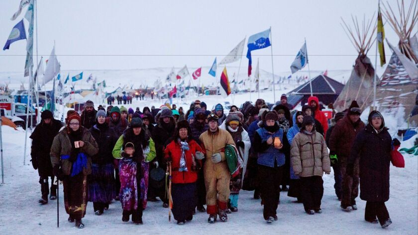 Beatrice Menase Kwe Jackson, center, and Daniel Emory, both of the Ojibwe Tribe, lead a procession to the Cannonball River in December as part of protests against the Dakota Access oil pipeline in Cannon Ball, N.D.