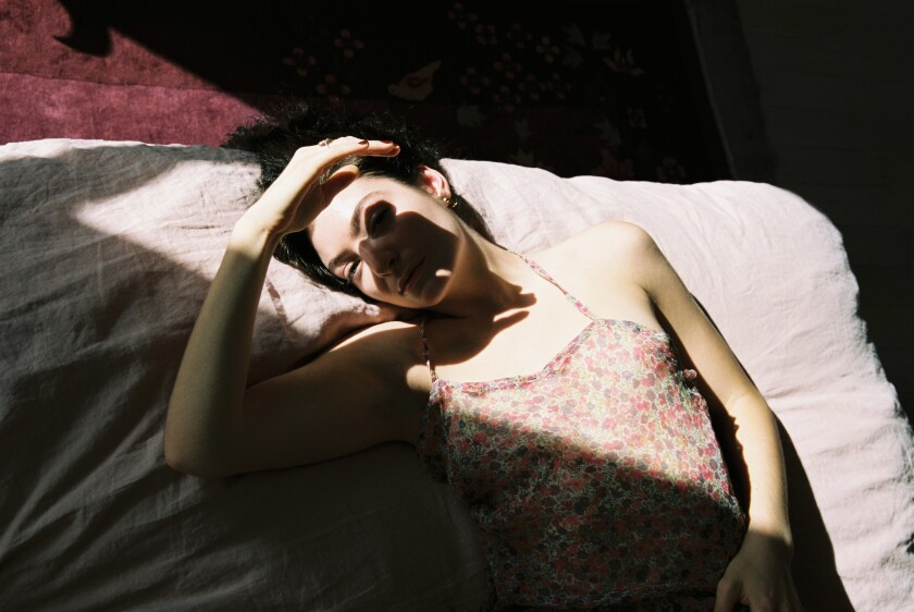 Lorde lies in the sun with her hand shading her face.