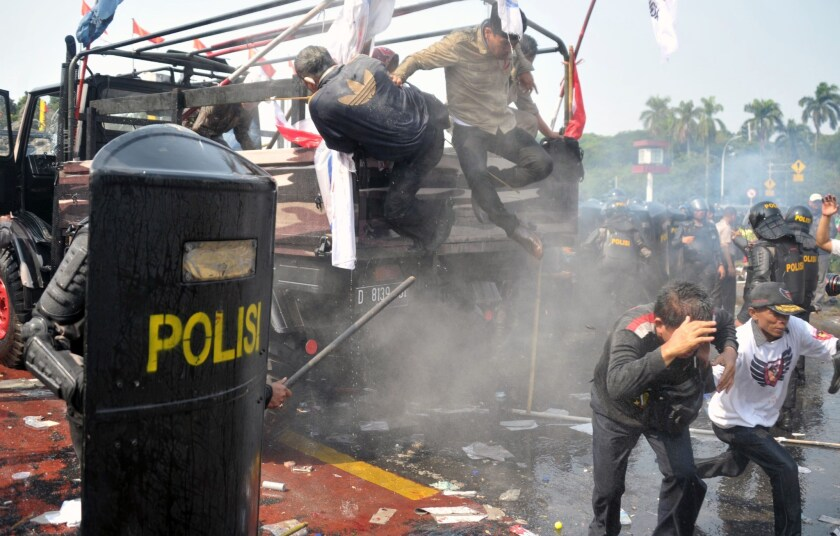 Indonesian anti-riot police move in to arrest supporters of presidential candidate Prabowo Subianto as they try to pass a blockade near the Constitutional Court in Jakarta on Thursday.