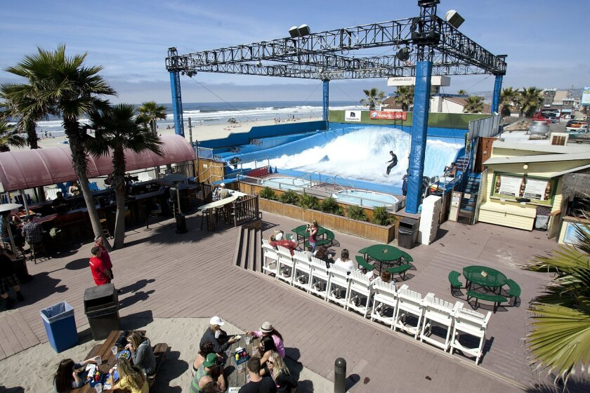 Diners enjoy lunch next to the wave machine at Belmont Park's Wavehouse in Mission Beach