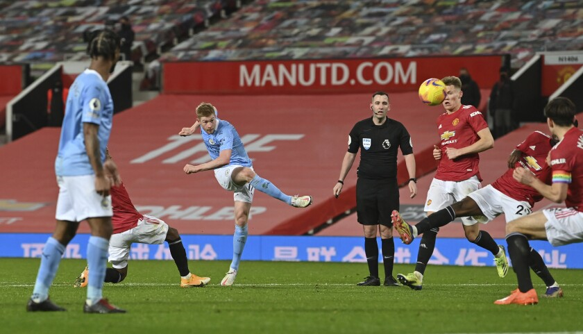 Manchester City's Kevin De Bruyne takes a shot at goal during the English Premier League soccer match between Manchester United and Manchester City at Old Trafford in Manchester, England. Saturday, Dec. 12, 2020. There have been 150 top-flight Man U v Man City derbies with United having won 58 and City 45, with 47 draws. (AP Photo/Paul Ellis/ Pool via AP)