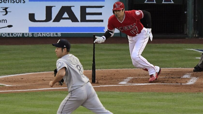 Angels designated hitter Shohei Ohtani hits a single as Seattle Mariners starting pitcher Yusei Kikuchi runs to back up the first baseman during the first inning on Saturday.