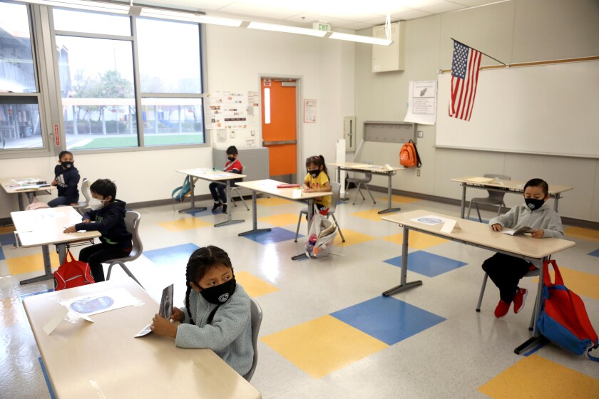 First-grade students attend class while sitting socially distanced and wearing masks