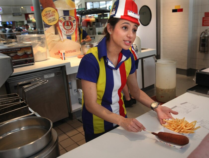 Alexia Haakma calls out an order ready at the Hot Dog on a Stick franchise at the Parkway Plaza Mall in El Cajon. The fast food place had a steady flow of hot dog lovers Thursday afternoon.