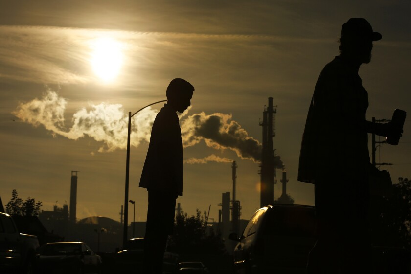 A boy and his grandfather stand near the Phillips 66 refinery in Wilmington.