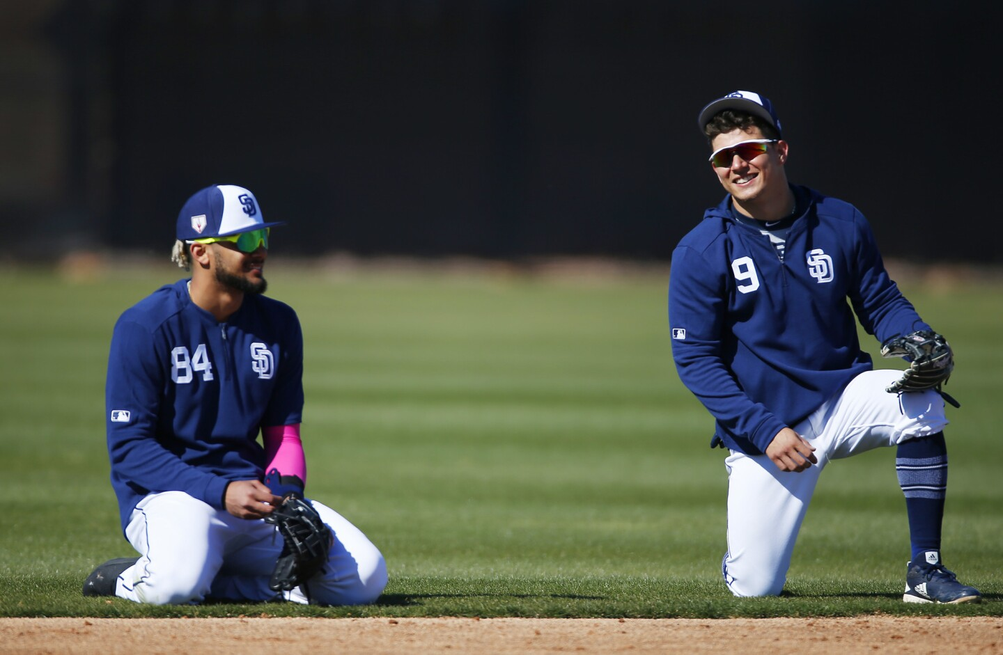San Diego Padres infielders Fernando Tatis Jr., left, and Luis Urias wait for drills during a spring training practice on Feb. 20, 2019. (Photo by K.C. Alfred/San Diego Union-Tribune)