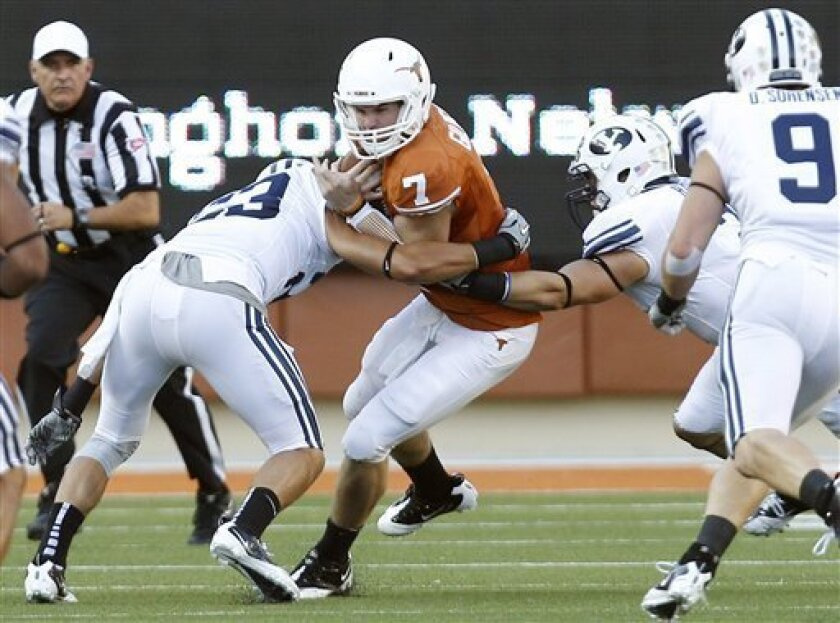Texas' Garrett Gilbert (7) is hit by BYU's Travis Uale, left, during the first quarter an NCAA college football game, Saturday, Sept. 10, 2011, in Austin, Texas. (AP Photo/Eric Gay)