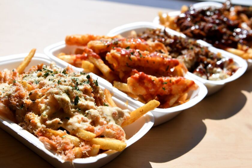 GARDENA, CALIFORNIA FEBRUARY 28, 2017-Lemon garlic snow crab fries, left, along with other choices at Mr. Fries Man in Gardena. (Wally Skalij/Los Angeles Times)