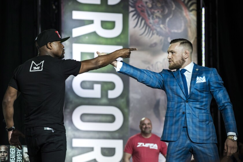 Floyd Mayweather Jr., left, and Conor McGregor exchange verbal jabs during a promotional stop in Toronto last month.