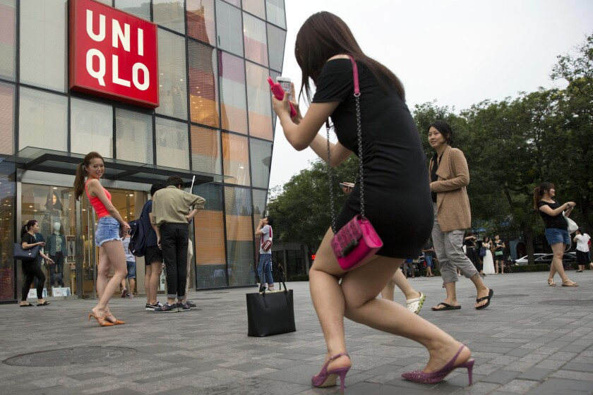 A woman poses for a photo outside the Uniqlo flagship store where a steamy video was purportedly taken.