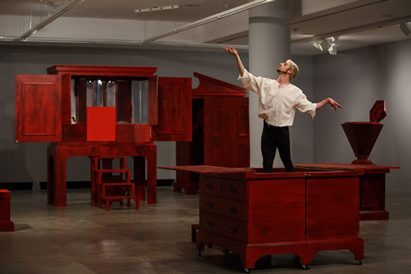 """A dancer maneuvers around and on furniture in Pablo Bronstein's """"Enlightenment Discourse on the Origins of Architecture,"""" at the Gallery at REDCAT in Los Angeles."""