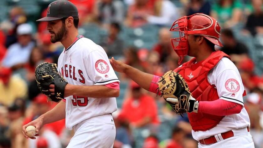Angels pitcher Nick Tropeano is visited by catcher Carlos Perez during the first inning Sunday.