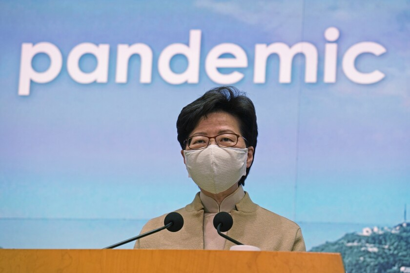 Hong Kong Chief Executive Carrie Lam speaks during a press conference in Hong Kong, Tuesday, Dec. 8, 2020. Lam says social distancing measures will be tightened as cases of the coronavirus continue to surge, with a ban on nighttime dining and more businesses ordered to close. (AP Photo/Kin Cheung)