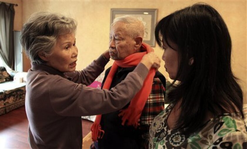 Shou-Mei Li, left, wraps a scarf around her husband Hsien-Wen Li, who is an Alzheimer's patient, as their daughter Shirley Rexrode, right, looks on, at their home in San Francisco, in this photo taken Thursday, Sept. 1, 2011.  Dementia is poised to become a defining disease of a rapidly aging popul