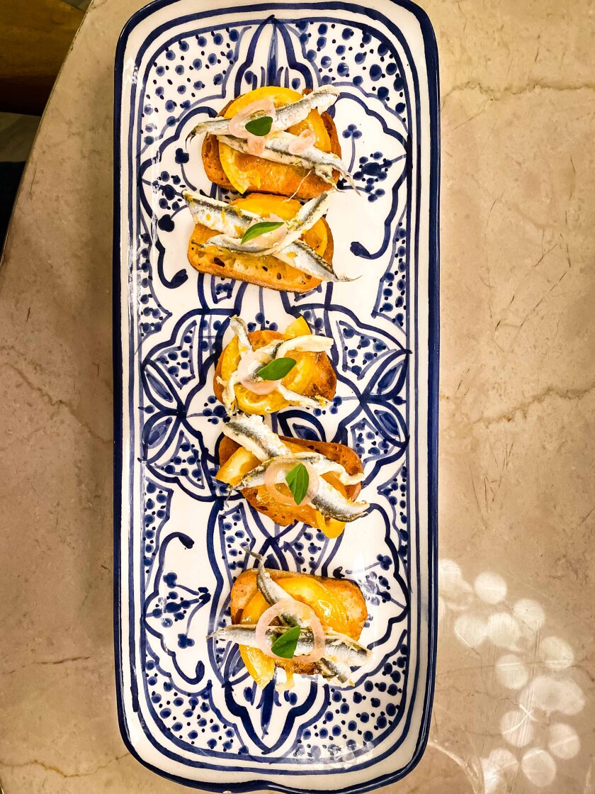 Crostini with tiny anchovies, shaved coins of tart preserved oranges and shaved ricotta salata