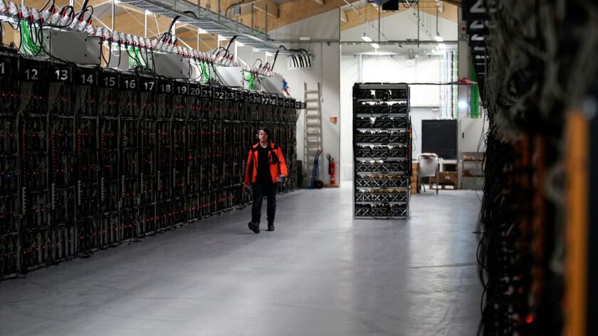 "A worker walks along a row of computer rigs that run around the clock ""mining"" bitcoin inside the Genesis Mining cryptocurrency mine in Keflavik, Iceland."