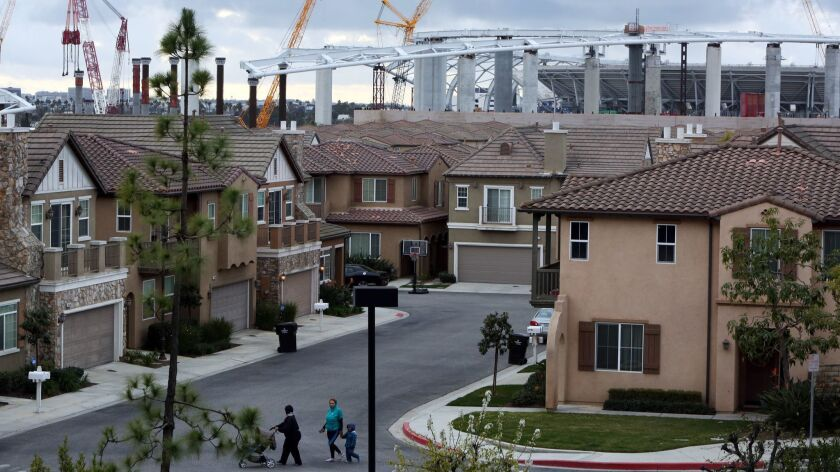 People cross the street in the Renaissance Homes, a gated community covering 37 acres in Inglewood, Calif. on February 20. Construction of the Rams-Chargers Complex is seen in the background.