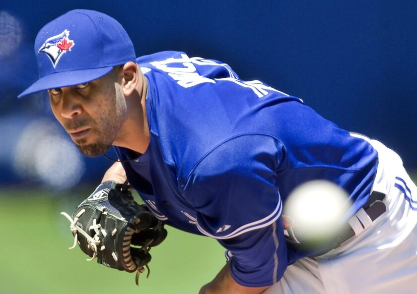FILE - In this Aug, 3, 2015, file photo, Toronto Blue Jays' new starting pitcher David Price works against the Minnesota Twins during the first inning of a baseball game in Toronto. Price is among the top players to join the AL East. (Fred Thornhill/The Canadian Press via AP, File)
