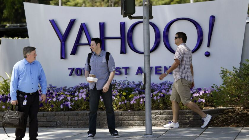 FILE - In this June 5, 2014, file photo, people walk in front of a Yahoo sign at the company's headq