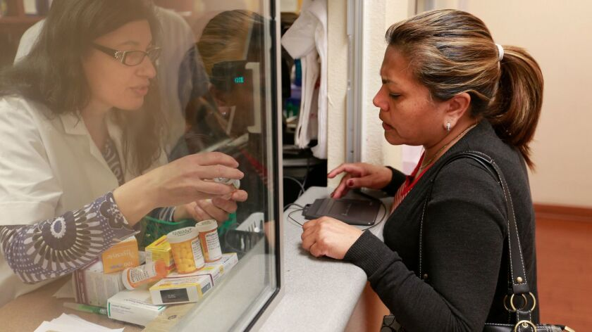 A patient has her prescription filled at AltaMed clinic in Los Angeles on March 11, 2015.