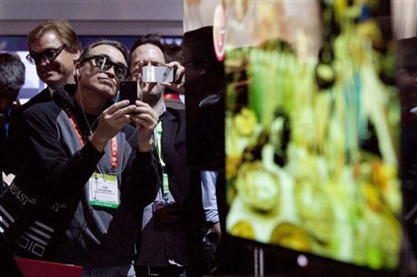 Industry affiliates make photos of the new LG 55-inch OLED television during the 2012 International CES Tradeshow, Tuesday, Jan. 10, 2012, in Las Vegas. (AP Photo/Julie Jacobson)