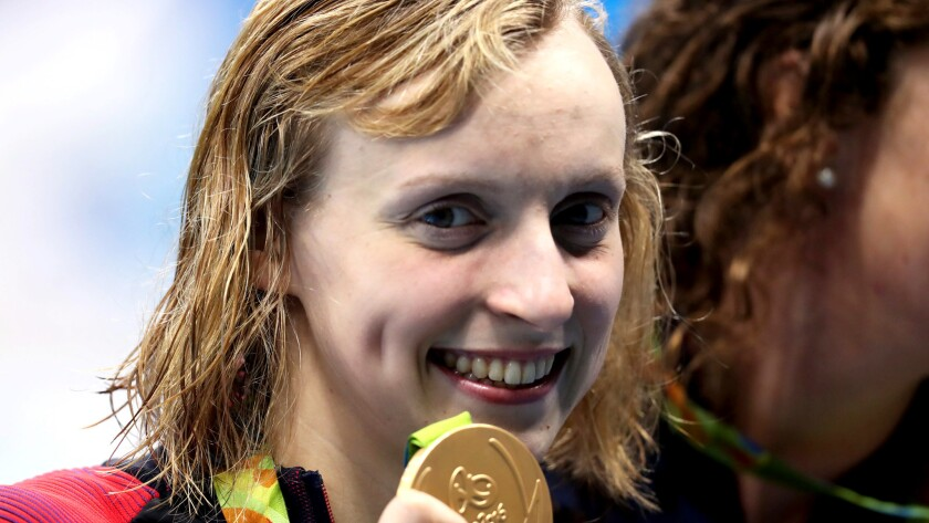 Katie Ledecky is all smiles after winning gold with her teammates in the 800-meter freestyle relay.