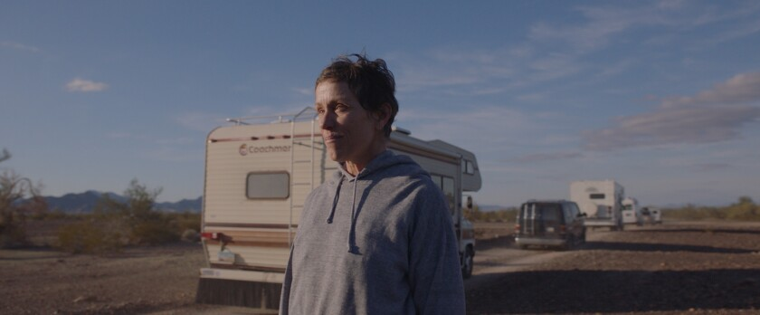 A woman stands near a line of RVs and vans.