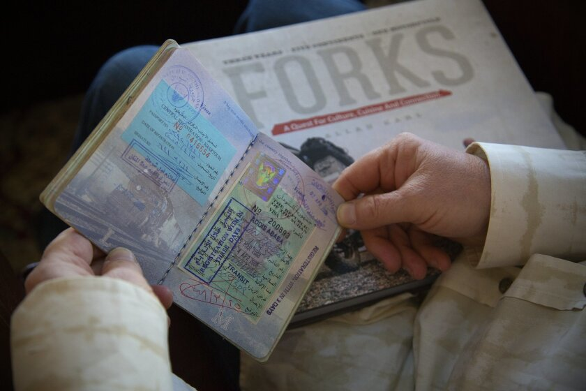 Allan Karl examines some of the travel visas pasted in his heavily stamped passport.