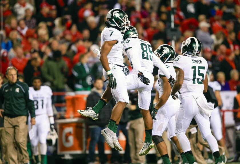 Michigan State defensive back Demetrious Cox (7) celebrates with teammate defensive end Evan Jones (85) after he intercepted a throw by Nebraska quarterback Tommy Armstrong Jr. during the first half of an NCAA college football game in Lincoln, Neb., Saturday, Nov. 7, 2015. (AP Photo/Nati Harnik)