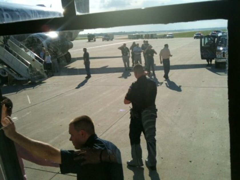 """This photo provided by Joey Mentzer, passengers are escorted off an Frontier Airlines plane on Sunday, Sept. 11, 2011 at Detroit's Metropolitan Airport. Police detained three passengers in Detroit after the crew of the Frontier Airlines flight from Denver reported suspicious activity on board and NORAD officials sent two F-16 jets to shadow the flight until it landed safely, the airline and federal officials said. Frontier Flight 623, with 116 passengers on board, landed without incident in Detroit after the crew reported that two people were spending """"an extraordinarily long time"""" in a bathroom, Frontier spokesman Peter Kowalchuck said. (AP Photo/Joey Mentzer)"""